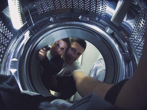 Mężczyzna z chłopcem wyjmują rzeczy z pralki